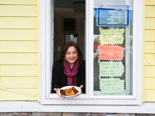 Ingrid Trujillo holds a traditional Guatemalan-style tamal, wrapped in a banana leaf, at Cache Tamales and Bakery on Wallace Road NW on Wednesday, Nov. 16, 2016. Trujillo opened the small stand two years ago.