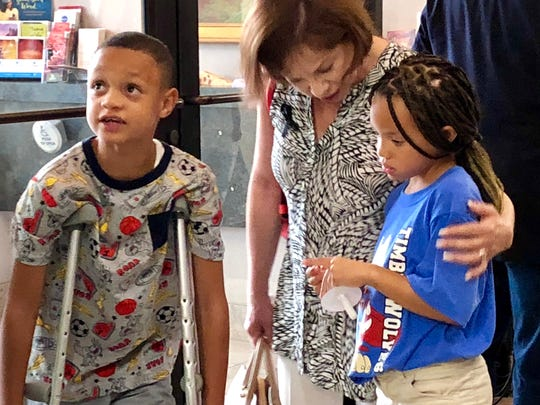 Justus Holland and his sister, Jasmine Holland, the children of Kharisma Ashlee James are greeted by Linda Mora, a grandmother of 2 children enrolled at Tippin Elementary School following a prayer vigil for James at Christ The King Presbyterian Church, 1500 N. Resler Drive Saturday.