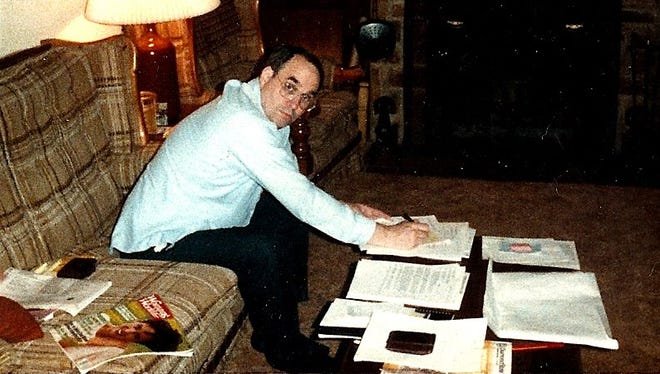 The author's dad doing some paperwork on the coffee table in the family's den in the 1980s.