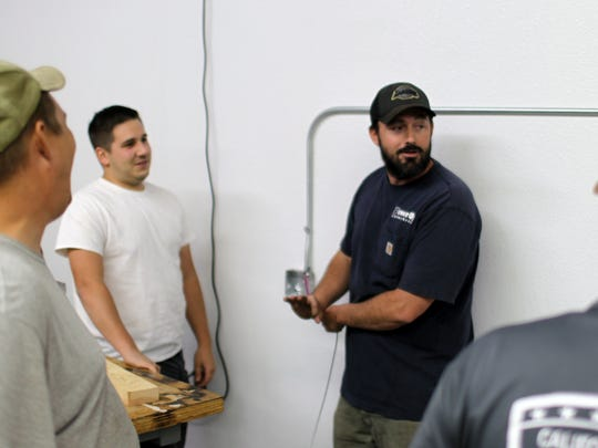 Chris Harrington, center, an instructor at the Shasta Builders' Exchange Trade School, demonstrates wiring techniques on a Monday night in September 2017 to students.