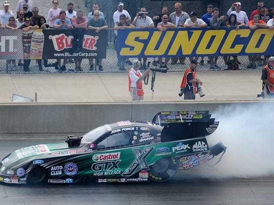 NHRA legend John Force smokes his tires while warming up for a pass during July's Summit Racing Equipment NHRA Nationals at Summit Motorsports Park in Norwalk . Force returns to the track Saturday night for the annual Night Under Fire show.