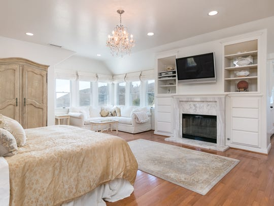The master suite's high ceilings, huge windows, recessed lighting and chandeliers combine to create a magical atmosphere. A gas fireplace with marble surround and crown molding mantle adds to the room's warmth and charm.