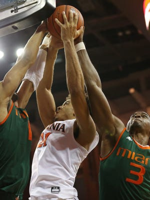 Virginia Cavaliers forward Isaiah Wilkins (21) is fouled while shooting the ball by Miami (Fl) Hurricanes guard Bruce Brown (11) with four seconds left in the second half at John Paul Jones Arena. The Hurricanes won in overtime 54-48.