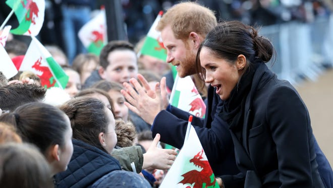 Prince Harry and Meghan Markle greet children waving Welsh flags on walkabout at Cardiff Castle on Jan. 18, 2018 in Cardiff, Wales.