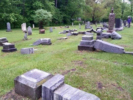 Several tombstones sit on their sides at the Immaculate Conception Parish cemetery on Church Road in Ira Township.