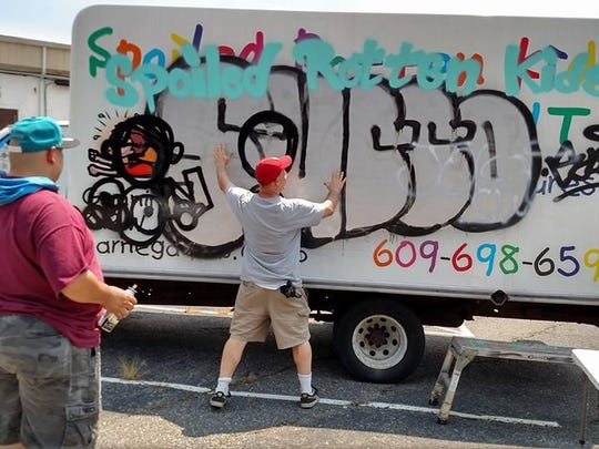 Artists Leon Rainbow and Michael Dybus plan to cover old graffiti using new at the Spoiled Rotten Kids Consignment truck in Barnegat.