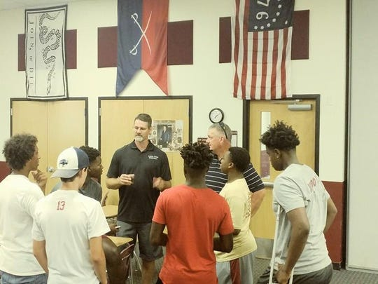 New Florida High boys basketball coach Todd McNeil, previously a 13-year head coach at Chiles, and assistant Sam Striplin, one a longtime Leon head coach, greet their new Seminoles team.
