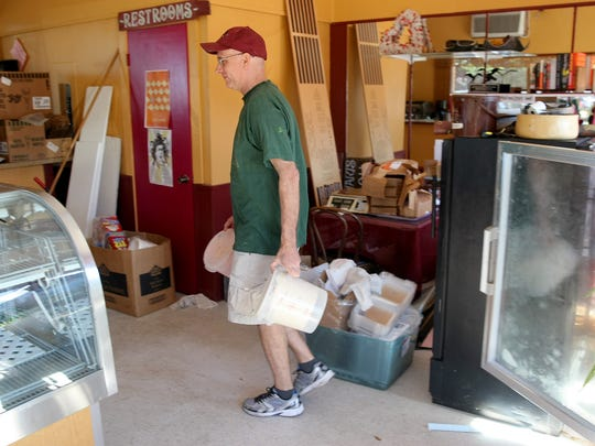 Matt Carter owner of Carter's Chocolates & Ice Cream moves tubs of ice cream to a display cooler in his new location  that he is getting ready to open at the Westbay Shopping Center in Port Orchard.