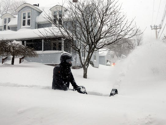 A homeowner wades through waist-deep snow as he snow