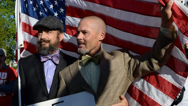 Joe and Frank Capley-Alfano of Oakland, Calif. hold a flag in front of the Supreme Court as oral arguments began in a collection of gay marriage cases.   Photo by H. Darr Beiser, USA TODAY Staff
