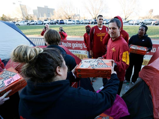 Iowa State head coach Steve Prohm hands Megan Sims, a junior from Pella, some pizza Tuesday, Dec. 8, 2015, as Prohm and some of his players hand out food to each tent dweller camped outside Hilton Coliseum waiting for the Cy-Hawk basketball game in Ames. Some of the students began camping out Monday night to be first in line for the Thursday night game against Iowa.