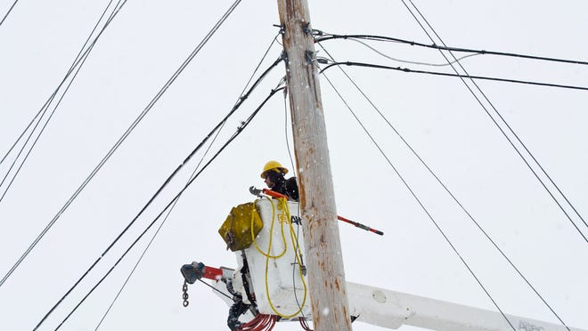 File photo of a Green Mountain Power employee working on a utility line.