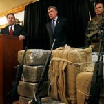 With seized drugs and weapons from border-crossing drug smugglers, Arizona Gov. Doug Ducey, left, speaks at a news conference after testifying at a field hearing of the U.S. Senate Homeland Security and Governmental Affairs Committee at the Arizona Capitol Monday, Nov. 23, 2015, in Phoenix.  R. Gil Kerlikowske, center, commissioner of the U.S. Customs and Border Protection, listens in during the news conference.