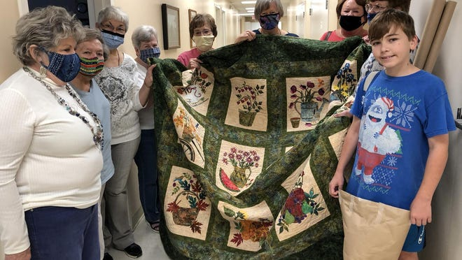 A group of volunteers holds up a quilt that will be auctioned off as part of this year's event.