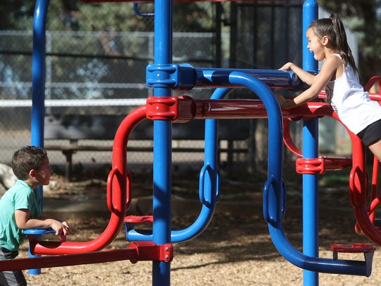 Jason Hartman, 3, and his sister Ava Hedayattzadeh, 7, play Monday at Alta Mesa Park in Redding.