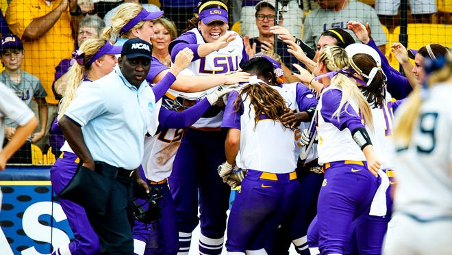 The LSU softball team mobs Bailey Landry after her two-run home run in the Tigers' 8-0 win over Arizona in the first game of the NCAA Super Regionals.