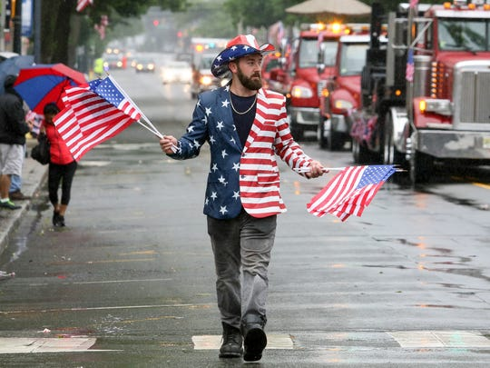 Sean Edwards of Bunky's Towing gives out flags during a very wet Memorial Day Parade in Dover on Monday, May 29, 2017.