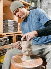 Joel Cherrico works on his new asteroid cups and meteorite mugs Friday, March 25, at his studio in St. Joseph.