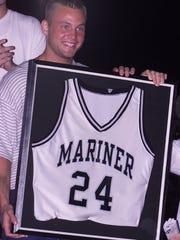 Dupay holds his former Mariner High School basketball jersey that was retired in this 2000 ceremony.