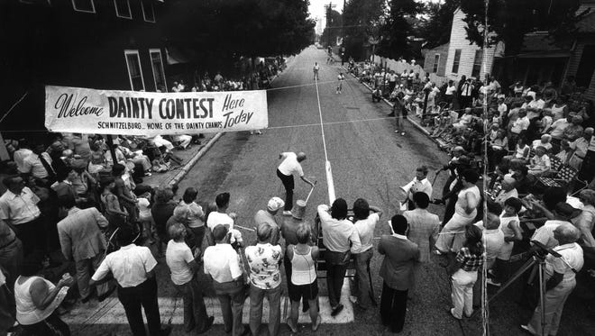 Spectators watch as Kenneth Rudloff tries to hit the dainty at the 10th Annual World Dainty Contest at Goss and Hoertz avenues in the Germantown/Schnitzelburg area.