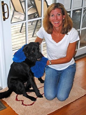 """Joanna Rein, of Larchmont, N.Y., poses at her home with her Labrador-collie named Buddy. Because Buddy was always tracking mud or water into the house, Rein created """"Soggy Doggy,"""" a doormat that absorbs most of the mess on the mutt. Rein has sold more than 300,000 mats online since 2010."""