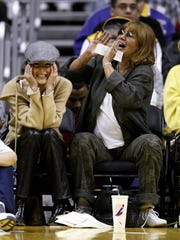 Actress Lara Flynn Boyle, left, and actress-director Penny Marshall attend the game between the LA Lakers and the Los Angeles Clippers on March 19, 2004 in Los Angeles, California.
