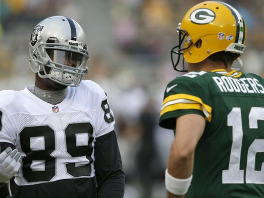 Green Bay Packers' Aaron Rodgers and Oakland Raiders' James Jones hang out prior to the start of the game.    The Green Bay Packers host the Oakland Raiders Friday, August 22, 2014, at Lambeau Field in Green Bay, Wis.  Dan Powers/Post-Crescent Media