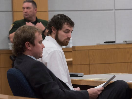 Charles McConnell, right, reads along with his attorney,