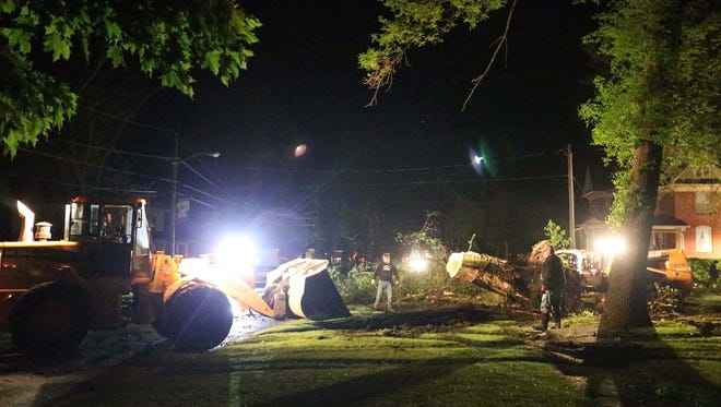 A group of people work to clear a fallen tree from a yard in Lake City late Sunday night, May 10, 2015 after a tornado ripped through town.