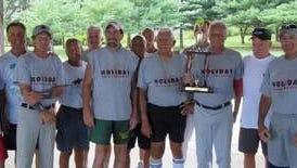 Holiday Service Center won the regular season and playoff titles in its division of the Berkeley Senior Softball League. Manager Charlie Dilkes holds the trophy awarded at the league's annual picnic.