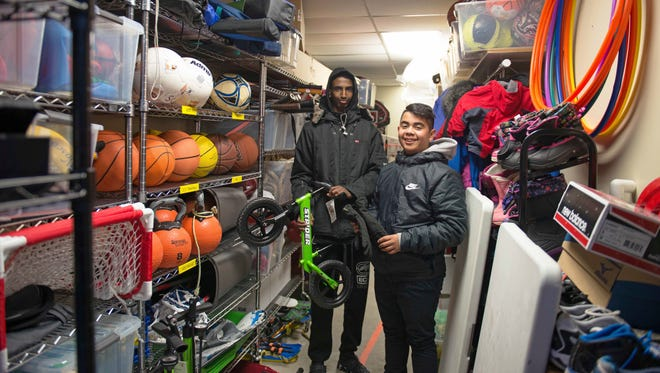 Hamsa Osman, left and Charly Tiempos, founders of Sports Check it Out, a sports equipment checkout program for kids in the Cedar Riverside neighborhood, stand with a variety of their equipment in Minneapolis on Feb. 4, 2018. (Easton Green/The Minnesota Daily via AP)