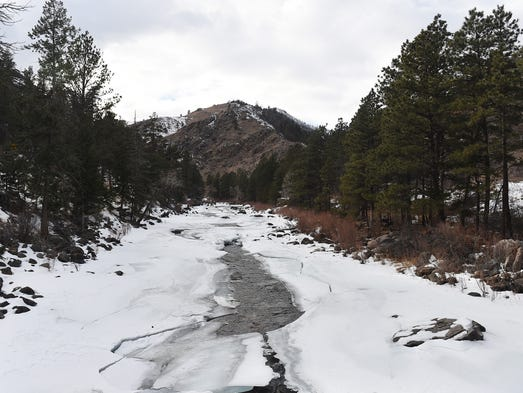 The Poudre River flows through broken layers of ice