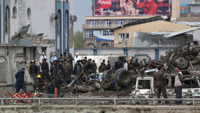 Afghan security forces inspect the site of a Taliban-claimed deadly suicide attack Tuesday in Kabul, Afghanistan, killing many and wounding more than 320 people.