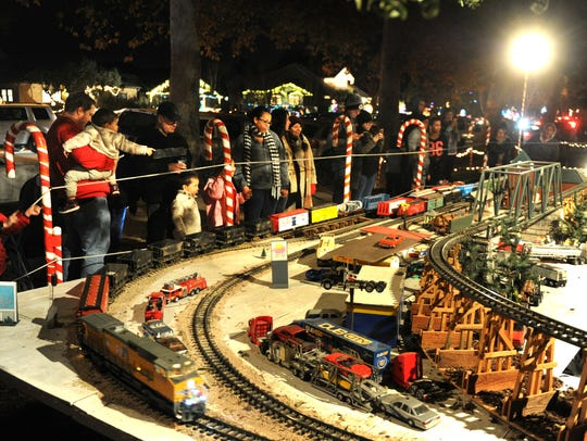 Model trains fill the front yard of a residence on