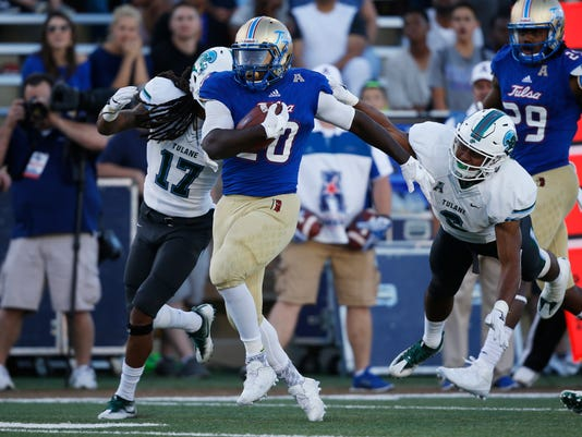 Tulsa running back James Flanders (20) carries past Tulane cornerback Parry Nickerson (17) and safety Jarrod Franklin (6) for a touchdown in the fourth quarter of an NCAA college football game in Tulsa, Okla., Saturday, Oct. 22, 2016. Tulsa won 50-27. (AP Photo/Sue Ogrocki)