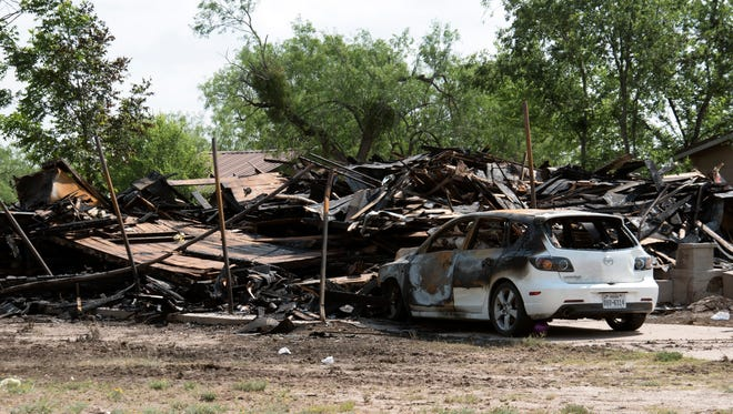 A burned out car sits in front of a house in the 500 block of Baker Street that was destroyed by fire early Tuesday.