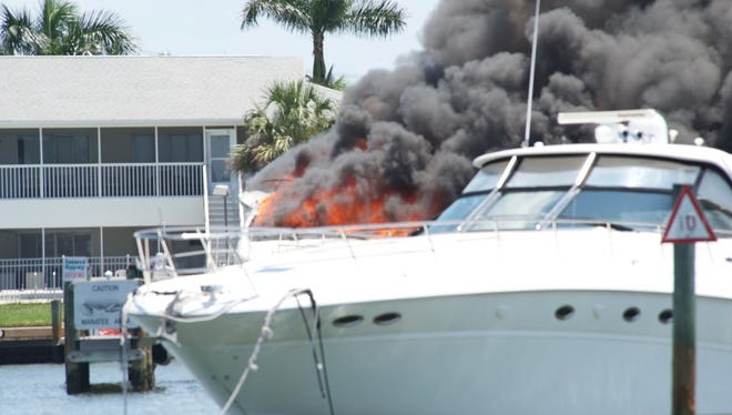 A boat that caught fire Monday afternoon at Capri Marina spews black smoke into the sky.