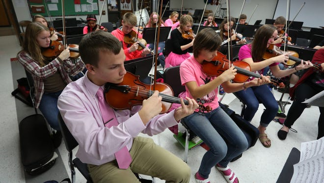 Violinists Luisa Marion, left, in plaid, and Jeffrey Hitchcock, wearing tie, are among the orchestra students that will be playing along with the Milwaukee-based band I'm Not a Pilot during a performance for the Vox Concert Series, Saturday night at the Marshfield High School auditorium. They are shown practicing with other orchestra members, Thursday, October 15, 2015.