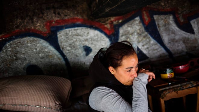 Jessica, a homeless heroin addict, wipes away tears as she describes how she tested positive for HIV after being raped last year in this spot under the bridge where she lives  in the Kensington neighborhood of Philadelphia, Pennsylvania, on April 14, 2017.