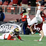 Stanford tight end Austin Hooper, right, leaps over Maryland defensive back Sean Davis.