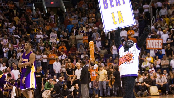 The Suns Gorilla holds a sign while Lakers guard Kobe Bryant waits for the end of a timeout during the 4th quarter of a 2007 game in Phoenix.
