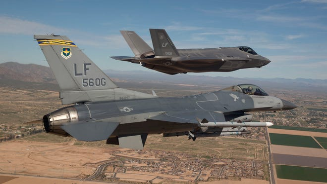 Maj. Justin Robinson flies the 56th Operations Group flagship F-16 Fighting Falcon as he escorts Luke Air Force Base's first F-35 Lightning II to the base March 10, 2014.