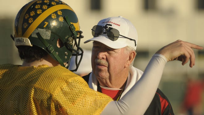 Former COS and Redwood football head coach Roger Kelly coaches a player during an all-star football practice in 2012. Five Tulare County teams still employ an offense that is similar to the one Kelly once ran.