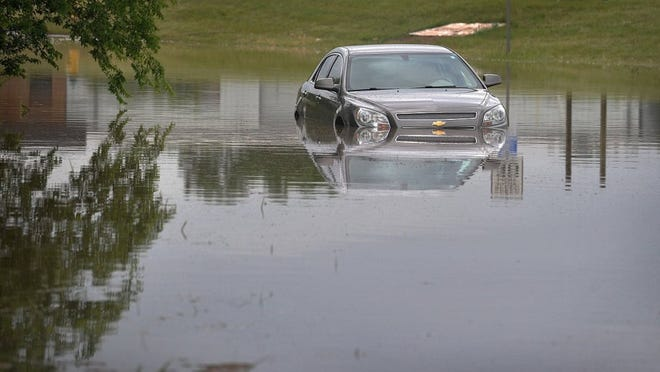 TORIN HALSEY/TIMES RECORD NEWS A motorist drove their car into high water near the intersection of East Hatton Road and Bonny Drive Monday morning before city crews could set up barricades for the rapidly rising waters.