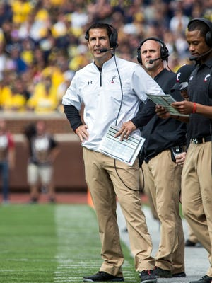 In this Saturday, Sept. 9, 2017, photo, Cincinnati head coach Luke Fickell, left, looks on from the sideline in the fourth quarter of an NCAA college football game against Michigan in Ann Arbor, Mich. Navy and Cincinnati met for the first time Saturday, Sept. 23, 2017, as American Athletic Conference opponents.