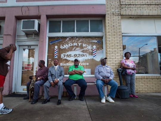 People sit outside of Shorty's Barbershop in Woodruff after watching a motorcade procession with the body of Sergeant Jeffrey Allan Sempler go by on Friday, April 22, 2016.