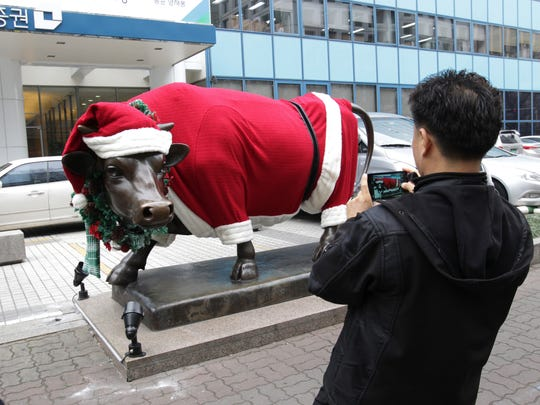 People photograph a bull statue decorated with a Santa