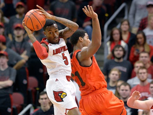 Louisville's Kevin Ware, left, pulls down a rebound next to Pikeville's Bruce Reed during the second half of an NCAA college basketball exhibition game.
