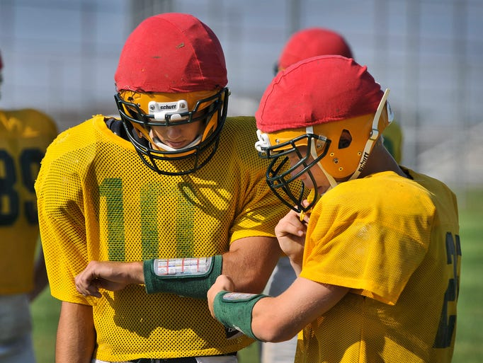 Sauk Rapids-Rice High School quarterback Jeremy Thorson (10) and running back Korey Keske (25) look over play information on their armbands as they work through team practice Wednesday, Aug. 20 at the school.