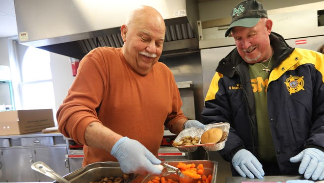 Walter Klotz of Ridgewood and Midland Park Mayor, Harry Shortway put together hot meals in Ridgewood before they are delivered to Community Meals, Inc. customers.  Wednesday, March 22, 2017